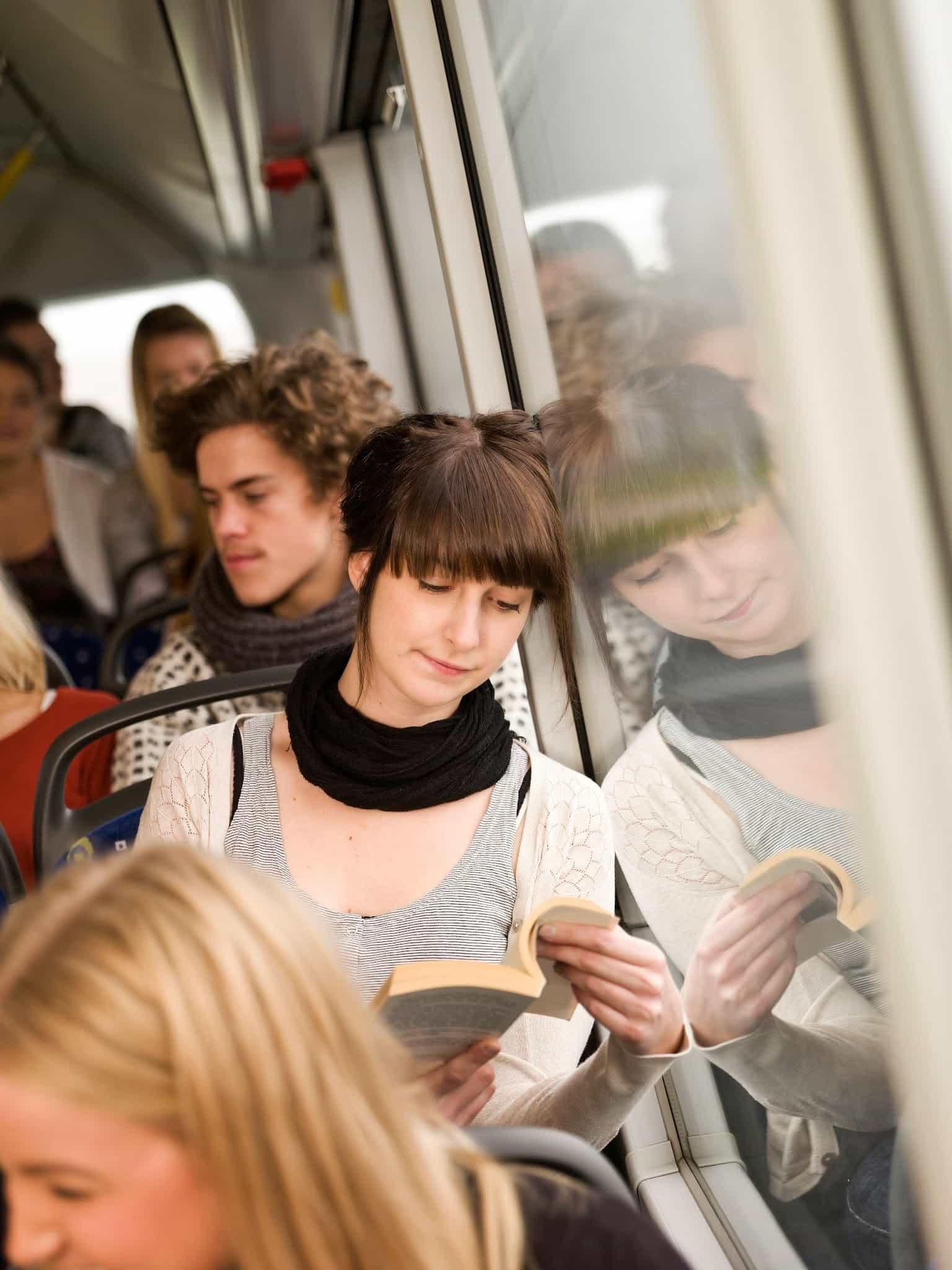 Mujer joven leyendo un libro mientras va en el autobús