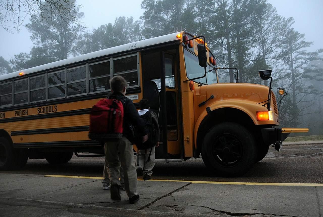 Niños abordando el bus, al lado de la via